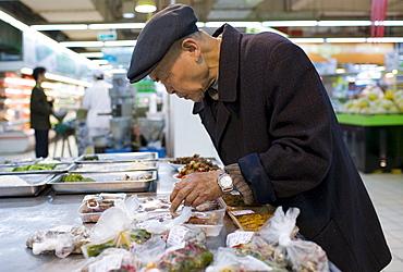 Man choosing shrink wrapped food in supermarket, Chongqing, China