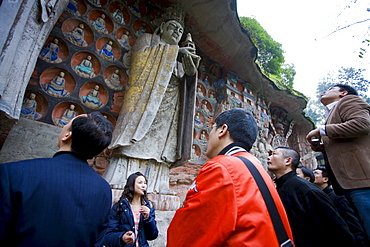 Tourists view Buddha statues Dazu rock carvings at Mount Baoding, Chongqing, China