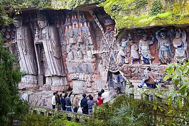 Tourist look at Anicca, God of Destiny holding wheel of life, Dazu rock carvings, Mount Baoding, China
