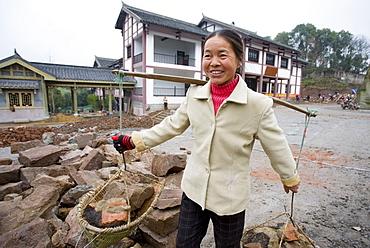 Woman at work building new tourist centre at Dazu Rock Carvings, Mount Baoding, Chongqing, China