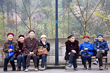 Elderly Chinese women sit together on benches in Chongqing, China