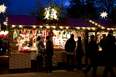 People shopping at traditional stall at Christmas market, Winter Wonderland, in Hyde Park, London