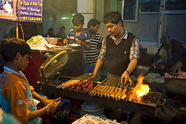 Food, meat kebabs, on sale at meat stall in Snack market at muslim Meena Bazar, in Old Delhi, India
