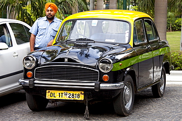 Sikh taxi driver with classic Ambassador taxi at The Imperial Hotel, New Delhi, India