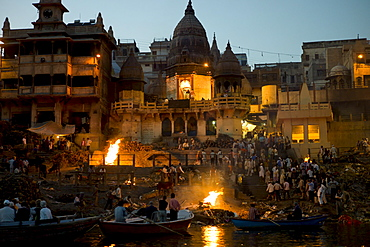 Tourists watch body bathed in River Ganges and traditional Hindu cremation on funeral pyre at Manikarnika Ghat in Holy City of Varanasi, Benares, India