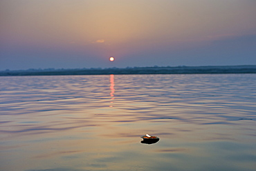 Ceremonial lit candle carries Hindu prayers on River Ganges at sunrise by holy city of Varanasi, Benares, Northern India