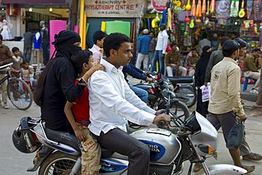Young Indian Muslim family ride motorcycle in street scene in city of Varanasi, Benares, Northern India