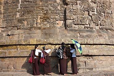 Buddhist visitors applying gold leaf as traditional offering at Dhamakh Stupa at Sarnath ruins near Varanasi, Benares, Northern India