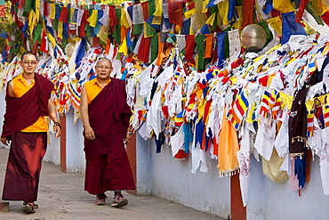 Buddhist monks pass prayer flags at Mulagandhakuti Vihara Temple at Sarnath near Varanasi, Benares, Northern India