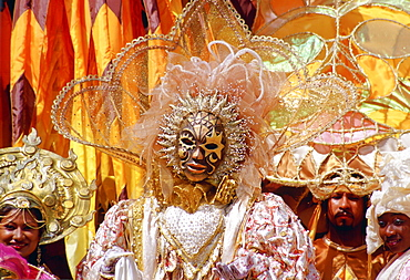 Carnival dancers wearing traditional costumes in pastel colours and gold in Trinidad, Caribbean