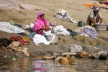 Indian man and woman doing laundry in the waters of The Ganges River at Cabua Pandey Ghat in City of Varanasi, Benares, India