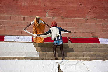 Indians doing laundry using the waters of the The Ganges River and the steps Kali Ghat in City of Varanasi, Benares, India