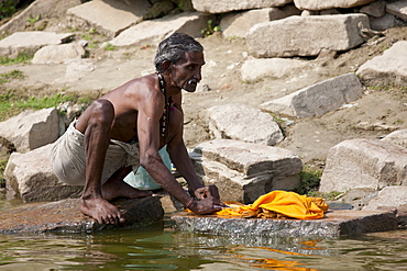 Indian doing laundry using traditional methods and the waters of The Ganges River at Kali Ghat in City of Varanasi, Benares, India