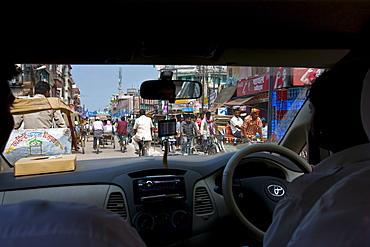 Busy street scene viewed through taxi windscreen in city of Varanasi, Benares, Northern India