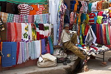 Stallholder selling clothes and sari fabrics and other textiles at Varanasi, Northern India