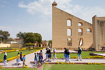 Students on a visit to The Observatory walk around the stone instruments in Jaipur, Rajasthan, Northern India