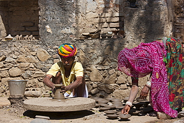 Indian potter in traditional Rajasthani turban works at home with his wife making clay pots in village of Nimaj, Rajasthan, Northern India