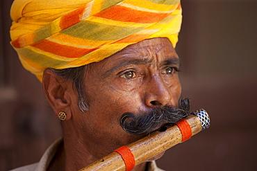 Hindu musician playing flute wind instrument at Mehrangarh Fort at Jodhpur in Rajasthan, Northern India