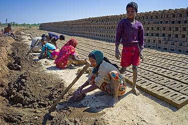 Indian family making bricks made from mud clay at Khore Bricks Factory, Rajasthan, Northern India