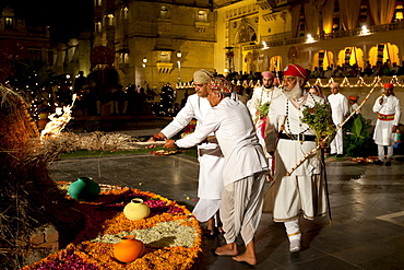 Shriji Arvind Singh Mewar of Udaipur, 76th Custodian of the House of Mewar, presides at annual Hindu Holi Fire Festival at The Zenana Mahal in the City Palace, Udaipur, Rajasthan, India. With him is son and heir Lakshyaraj Singh Mewar of Udaipur, Maharaj Kumar and Hindu priests