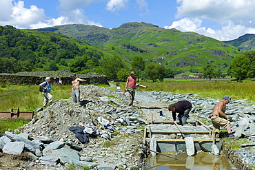 Workers pitching a path using Elterwater green slate, near Easedale Tarn in the Lake District National Park, Cumbria, UK