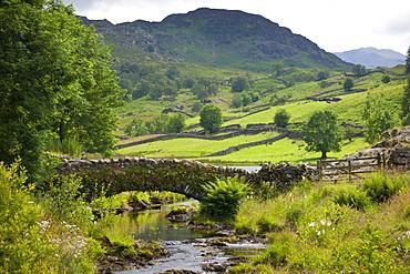 Packhorse Bridge across mountain stream at Watendlath in the Lake District National Park, Cumbria, UK
