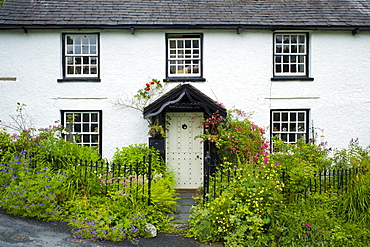 Quaint lakeland cottage with studded front door and Welcome sign, at Troutbeck in the Lake District National Park, Cumbria, UK