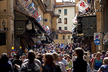 Crowds cross the Ponte Vecchio from the north side of the River Arno, Florence, Tuscany, Italy