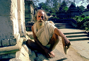 A holy man crouching at the Pashupatinath Temple on the Bagmati River in Nepal.  It is one of the holiest Hindu Temples in the world.