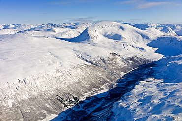 Aerial view of arctic landscape, snow covered road and Lyngen Alps from aircraft approaching Tromso in the Arctic Circle in Northern Norway