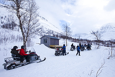 Pitstop for snowmobiling group among arctic alps in the Arctic Circle near Holt in the region of Tromso, Northern Norway