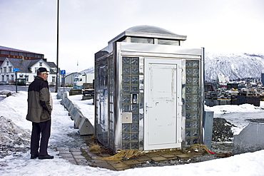 Man gazes at futuristic design Public Convenience toilet in Tromso, Norway