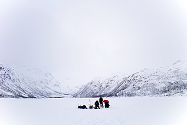 Ice fishing on frozen lake in the arctic alps in the Arctic Circle on Ringvassoya Island in the region of Tromso, Northern Norway