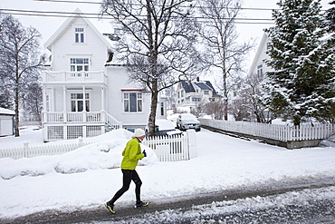 Local woman jogging in Jonas Lies Gate, the elegant  residential area of Tromso within the Arctic Circle in Northern Norway