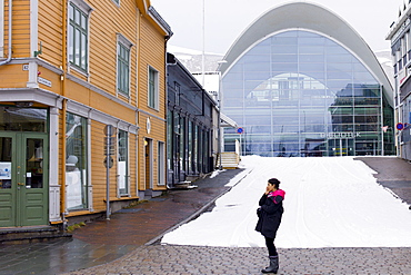Local woman using mobile phone in street scene by modern Biblioteket library in Tromsoya, Tromso, in Northern Norway