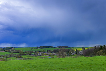Rainstorm from Cumulonimbus cloud above Asthall Village in springtime in the Cotswolds, Oxfordshire, UK