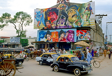 "Street scene in Islamabad, Pakistan showing rickshaws, an old two-tone Morris Minor car and the local cinema advertising films often described as ""Bollywood'."