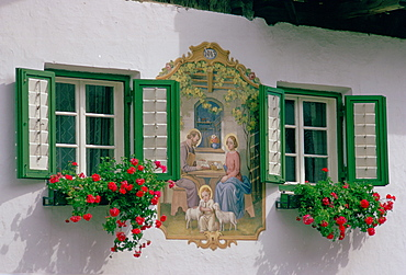 In the Austrian Tyrol a farmhouse mural depicting baby Jesus with a halo hugging lambs with his parents Mary and Joseph nearby.This religious mural  painted in 1943  is sited between two flower troughs planted with geranium plants below windows with shutters.