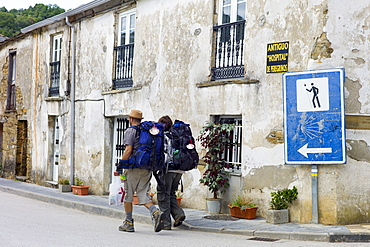 Couple pass sign on Camino de Santiago Pilgrim's Way to Santiago de Compostela at Triacastela in Galicia, Spain