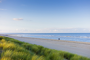 Couple stroll along deserted and peaceful Utah Beach, scene of the D-Day Landings,  in Normandy, France