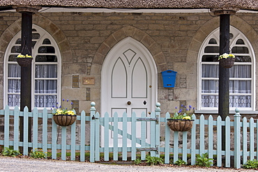 Quaint traditional cottage with thatched roof, gothic style arched door , hanging baskets and paling fence, Cornwall, England, UK