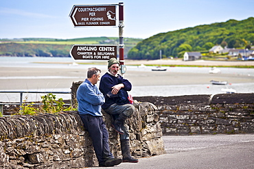Locals chatting in the Gaelic language on the quayside at Courtmacsherry in County Cork, Ireland