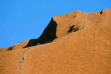 A lone visitor holding the handrail for his descent of steep Ayers Rock, Australia