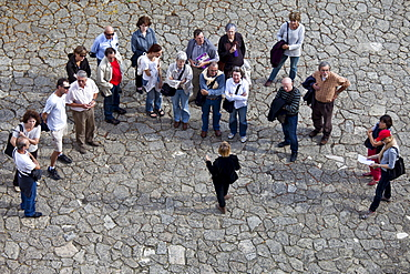 Tourists listen to tour guide in quaint street in St Emilion, Bordeaux, France