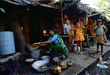 Watched by a group of young children a woman washes dishes in a bucket of water at a humble home on the sidewalk in Bombay, India.  A little girl has a gleeful expression despite the poverty of the situation.
