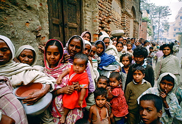 Women carrying pots with children in early morning food queue at Mother Teresa's Mission Calcutta, India
