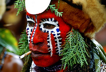 Tribesman with painted face and a cigarette in Papua New Guinea