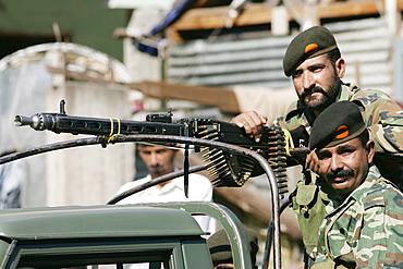 Armed Pakistani soldiers with machine gun  in village of Pattika, Pakistan
