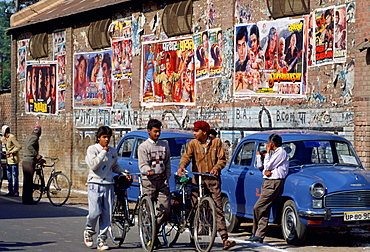Bollywood ' film posters advertising the latest movies in Agra, India.  Young men chatting together while pushing their bicycles.