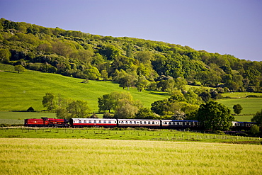 Traditional old steam engine locomotive train with carriages in Cotswolds countryside near Winchcombe in Gloucestershire
